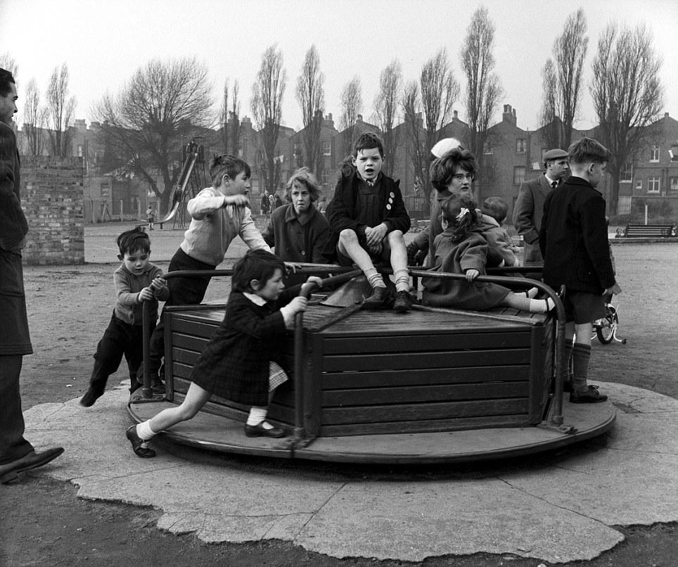 CHILDREN PLAYING IN PLAYGROUND - 1950S