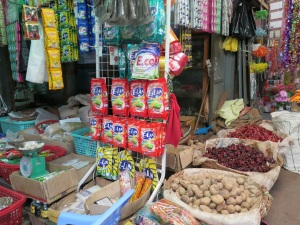 Sachets of detergent alongside potatoes and chillies