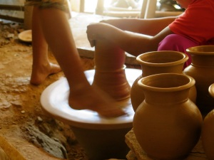 The pottery wheel is kept in motion by one worker pushing the wheel with her right foot.  A small rope from the roof helps her to keep her equilibrium